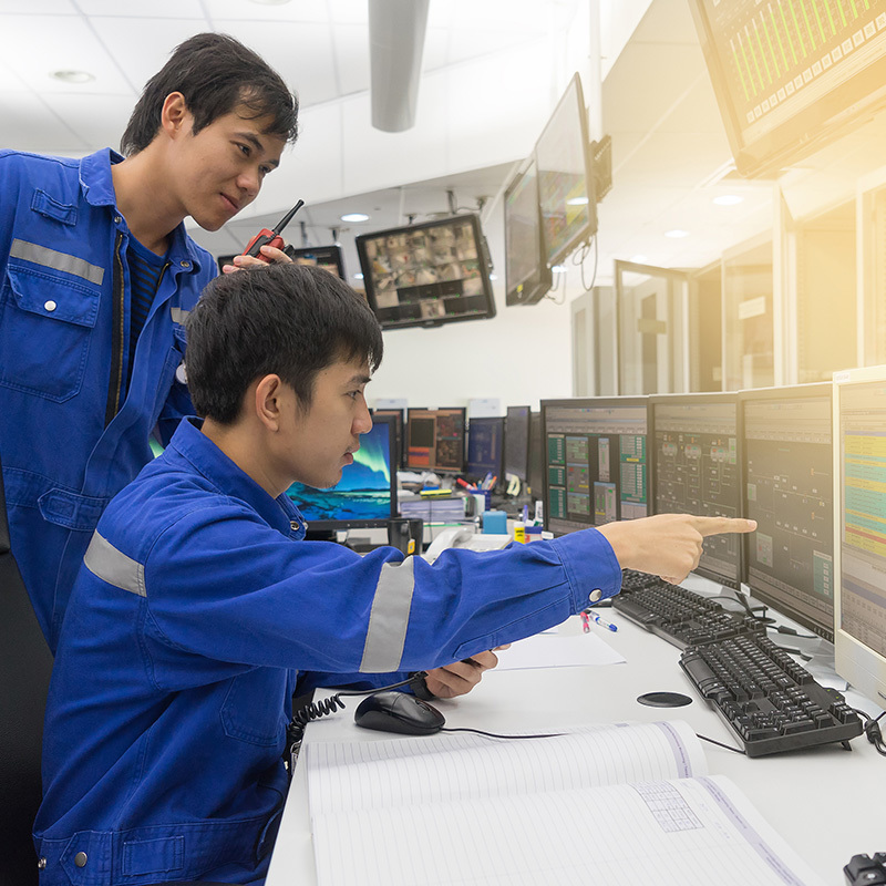 Picture of two men looking at a SCADA screen in a control room
